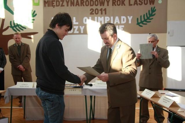 Nagrodę za udział w konkursie o lasach zorganizowanym w SP2 w Sycowie wręcza Pawłowi nadleśniczy Józef Szymański