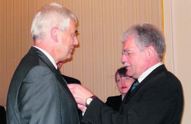 Wojewoda Stanisław Kracik dekoruje Złotym Krzyżem Zasługi starostę oświęcimskiego Józefa Kałę (z lewej)
