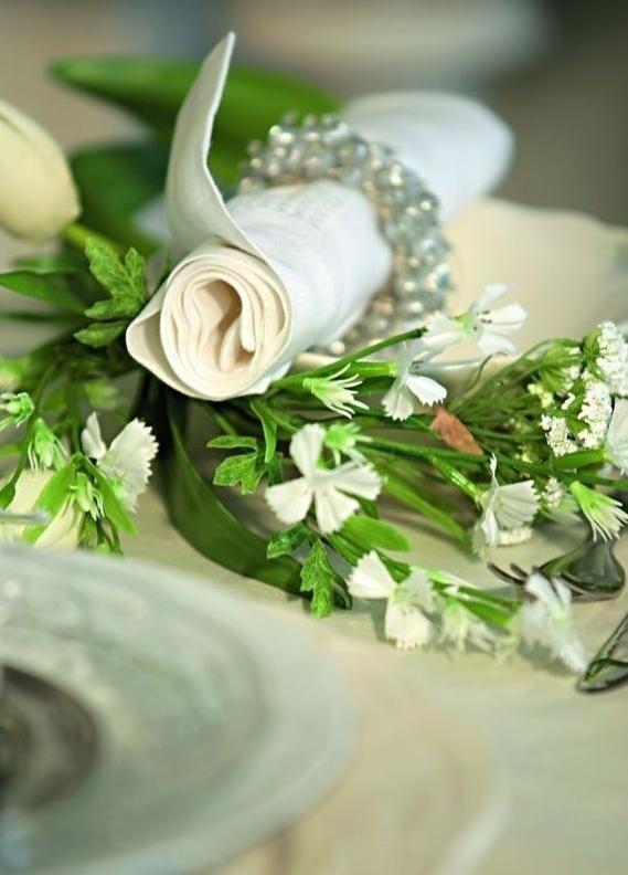 Na zrolowane serwetki z materiału nałożono obrączki z perłowych koralików. Każda z nich została położona w miseczce i otulona zielenią – dużymi dekoracyjnymi liśćmi i gałązkami drobnych białych kwiatków.