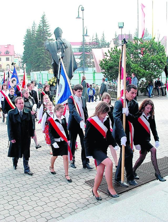 Uczniowie ze sztandarami swoich szkół w drodze na mszę