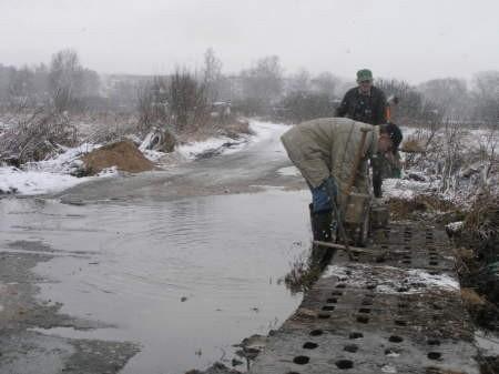 Pracownicy interwencyjni położyli chodnik na krawędzi zalewanej drogi. FOT. MATEUSZ WĘSIERSKI
