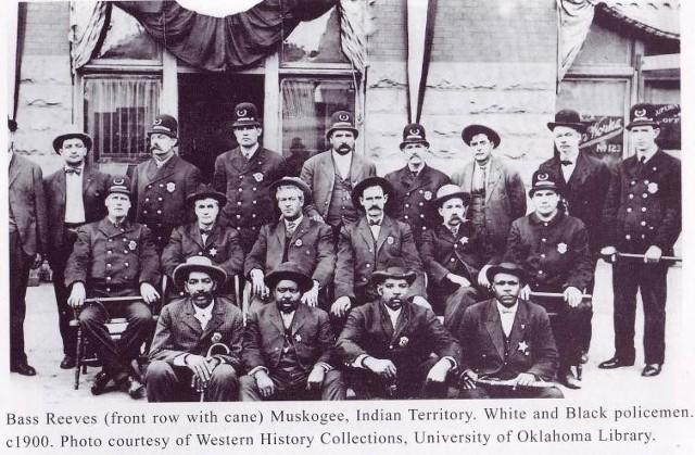 Bass Reeves (w pierwszy rzędzie,pierwszy z lewej) z grupą innych policjantów ok. 1900 roku.