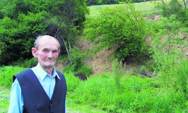 Edward Szlag z Koniuszowej stoi w pobliżu miejsca, gdzie potok Łęgówka podmywa kilkudziesięciometrowy stok góry Wisyny. W tle za drzewami zbudowano zbiornik na wodę