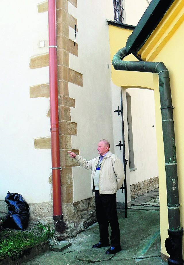Kościelny Stefan Bożek pokazuje nowe rynny z plastiku