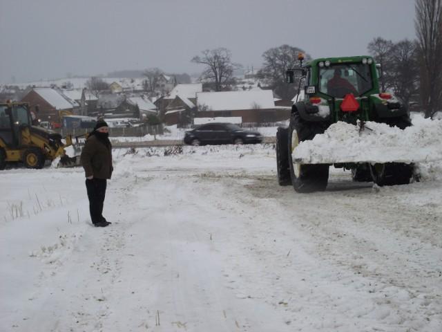 Ciężki sprzęt przygotowuje pole przy drodze na potrzeby narciarzy.