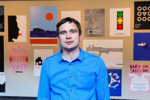 Maciej Kurak w budynku Uniwersytetu Artystycznego. W tle wystawa studenckich plakatów, z których wiele poświęcono... Euro 2012.