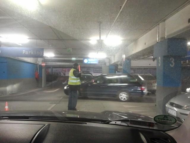Na parkingu w CH King Cross Marcelin w Poznaniu parkingowy kieruje ruchem, aby ułatwić klientom wyjazd z galerii