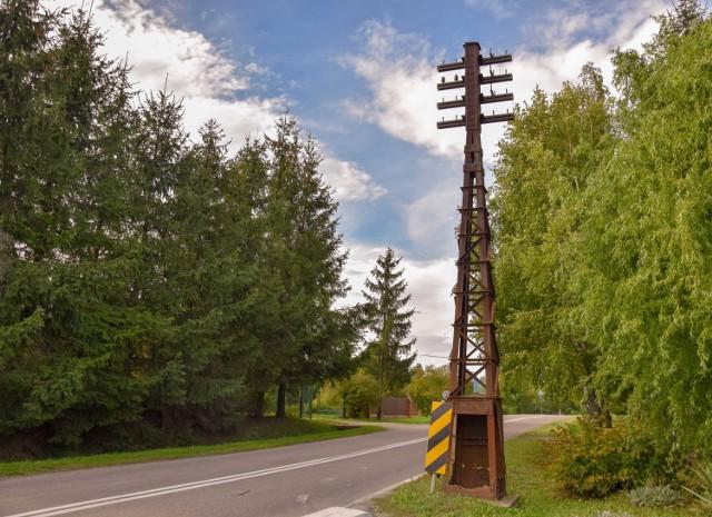 Zabytkowy słup telefoniczny z czasów Twierdzy Przemyśl stoi i niszczeje przy ruchliwej drodze.
