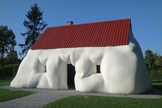 """Rzeźba zatytułowana """"Gruby dom"""" powstała w 2003 r. i według artysty ma stanowić ironiczny komentarz na temat tego, jak duży nacisk kładziemy czasem na imponowanie sąsiadom swoją zamożnością. Dla rzeźbiarza absurdalne jest budowanie czy kupowanie większych domów """"na pokaz"""", dlatego stworzył imponujących rozmiarów dom, który jednak zamiast podziwu budzi śmiech.  Licencja"""