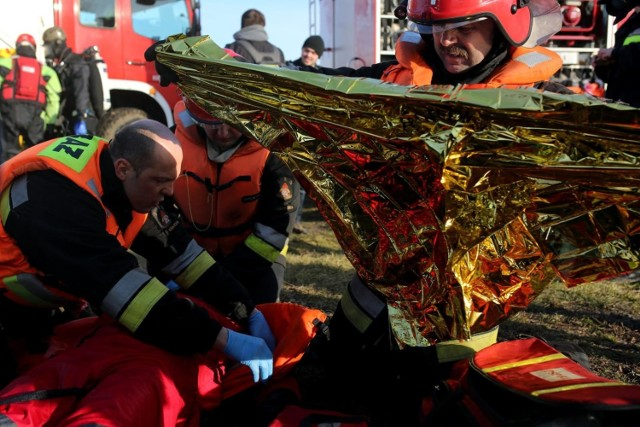 Cudem z wypadku wyszedł 25-letni kierowca porsche cayenne, który w nocy z piątku na sobotę (z 15 na 16 stycznia) stracił panowanie nad pojazdem i wpadł do zamarzniętego stawu.   Do groźnego wypadku doszło na drodze między miejscowościami Lisiewice Duże a Guźnia pod Łowiczem. Auto przebiło zewnętrzną warstwę lodu i zanurzyło się w wodzie.   Było ok. godz. 23, gdy 25-latek  kierujący czarnym porsche stracił nad nim panowanie, zjechał z drogi i wpadł do głębokiego na 2 metry stawu hodowlanego. W momencie wypadku temperatura powietrza wynosiła -8st. C. Na szczęście kierowca zdołał o własnych siłach szybko opuścić auto, wydostać się na brzeg i wezwać pomoc Mężczyzna był przemoczony i zziębnięty - nie odniósł żadnych obrażeń.   Na miejsce zadysponowano zastępy z JRG Łowicz oraz OSP Rogóźno, które w pierwszej kolejności udzieliły pomocy 25-latkowi Z relacji strażaków wynika, że  w specjalistycznych kombinezonach weszli oni do skutej lodem wody, by zaczepić linę i wyciągnąć pojazd. Do akcji zadysponowano dodatkowo ciężki samochód ratownictwa technicznego z JRG Stryków. Ostatecznie dzięki użyciu specjalnego wysięgnika udało się wydobyć porsche przed godz. 2.   Policjanci z KPP w Łowiczu sprawdzili trzeźwość 25-latka - była bez zarzutu. Funkcjonariusze ukarali go mandatem za spowodowanie kolizji.  ZDJĘCIA Z MIEJSCA ZDARZENIA - KLIKNIJ DALEJ
