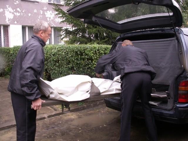 Pracownicy zakładu pogrzebowego wynoszą do samochodu zwłoki jednej z ofiar