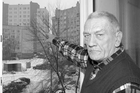 Janusz Neugebauer pokazuje z okna swojego mieszkania sàsiedni blok, z którego już odpadło kilka płyt.