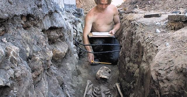 Krzysztof Ptok dokumentuje znalezisko w grobie dorosłego mężczyzny.