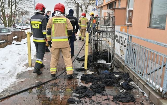 """We wtorek około godziny 15 doszło do pożaru i wybuchu w kompleksie sklepów przy ulicy Warszawskiej w Kielcach, na osiedlu Uroczysko.    <script async defer class=""""XlinkEmbedScript""""  data-width=""""640"""" data-height=""""360"""" data-url=""""//get.x-link.pl/b2d2a208-f5df-0318-896c-9ecd1c0808cb,1c40a22a-9236-078a-3636-55af4a9d2515,embed.html"""" type=""""application/javascript"""" src=""""//prodxnews1blob.blob.core.windows.net/cdn/js/xlink-i.js?v1"""" ></script>  Mariusz Góra, zastępca komendanta miejskiego kieleckiej straży pożarnej przekazywał: - Doszło najprawdopodobniej do wybuchu, gdyż uszkodzona została stolarka okienna w jednym z pawilonów handlowych. Był niewielki pożar i panowało zadymienie, ale sytuacja jest już opanowana. Ustalamy obecnie przyczynę zdarzenia – dodawał Mariusz Góra.  Jak na gorąco informowali strażacy pożar wybuchł w pralni a zagrożenie było tym większe, że znajdowało się tam sporo materiałów chemicznych   W momencie zdarzenia w budynku pralni były cztery pracownice, które zdołały wyjść z pomieszczenia o własnych siłach. - Miały delikatnie opalone włosy, zostały przebadane przez załogę karetki pogotowia, ale nic im się nie stało – wyjaśniał wiceszef kieleckich strażaków.  Niewielkie obrażenia odniósł też przechodzień, który w chwili wybuchu znajdował się obok pawilonu. I on został opatrzny przez ratowników medycznych na miejscu.  - Nasze wstępne ustalenia wskazują, że prawdopodobnie doszło do wybuchu oparów z tkanin do czyszczenia, które z jednej z firm przewieziono do pralni, aby je wyprać. Mieszkania oparów z ulatniająca się z tych tkanin spowodowała wybuch i pożar – tłumaczył Mariusz Góra.  Eksplozja sprawiła, że okna pralni wypadły z futryn i upadły kilka metrów dalej, na pas zieleni za chodnikiem. Doszło też do delikatnych pęknięć na ścianach wewnątrz budynku. - Na miejscu pracował Inspektor Nadzoru Budowlanego dla miasta Kielce, który oceni czy doszło do poważnych uszkodzeń w konstrukcji budynku i czy będzie się on nadawał do dalszej eksploatacji – zaznaczał komen"""