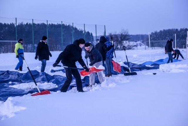 Kibice Arki Gdynia chwycili za łopaty, inny sprzęt i zabrali się dziś za odśnieżanie trawiastego boiska w Chwaszczynie.