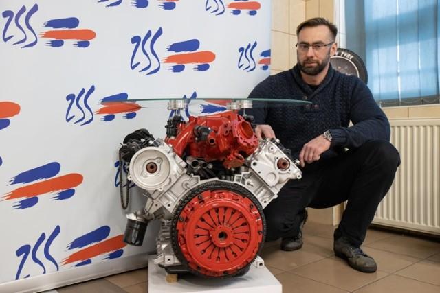 Mariusz Rakowicz, nauczyciel kształcenia zawodowego w Zespole Szkół Samochodowych, prezentuje stolik wykonany przez uczniów, którego podstawą jest silnik V6.