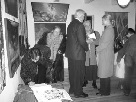Do księgi pamiątkowej wpisuje się Zofia Kosińska. Za nią czeka Ryszarda Nowakowska. Obok profesor Marian Bietkowski w rozmowie z Marią Zakrzewską.