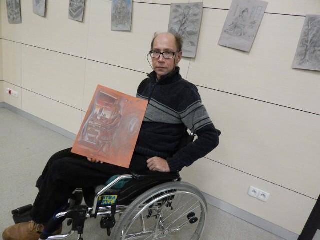 -Jestem niepełnosprawny i bezdomny, ale pomysłów na prace mam mnóstwo. Taka wystawa była strzałem w dziesiątkę - przyznaje Arkadiusz Szymków-Stawnicki. Na zdjęciu na tle swoich rysunków.