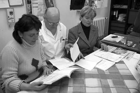 Barbara Sachogłuchowicz, Aleksander Stankowski i Elżbieta Żuchowicz przeglądają finansowe sprawozdania  dąbrowskiego szpitala.