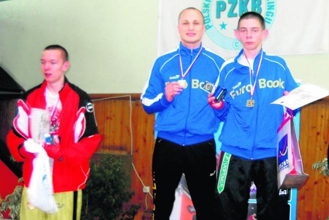Na najwyższym stopniu podium stoją, od lewej: trener Łukasz Smoliński i Kamil Tornado Szłapka