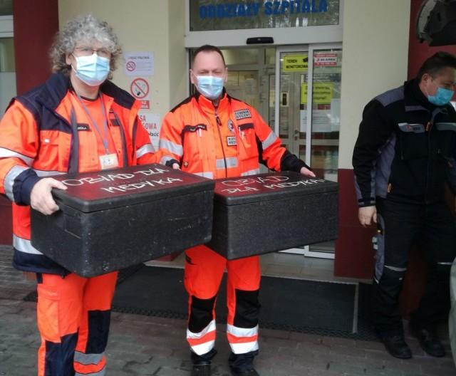 Ratownicy medyczni z kolejną porcją posiłków w pojemnikach utrzymujących ciepło