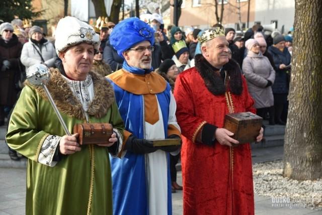 """Piękny Orszak Trzech Króli 2020 przeszedł ulicami Buska - Zdroju 6 stycznia. Wzięli w nim udział licznie mieszkańcy miasta z trzech parafii, ale także wierni z okolicznych miejscowości. Wszyscy spotkali się na wspólnym kolędowaniu przed budynkiem Starostwa Powiatowego. Tegorocznemu orszakowi w całym kraju towarzyszyło hasło: """"Cuda, cuda ogłaszają!"""" - więc nie zabrakło do niego nawiązań podczas mszy świętych poprzedzających orszak.    W rolę Trzech Króli wcielili się: Waldemar Sikora-burmistrz miasta i gminy Busko-Zdrój, Jerzy Kolarz – starosta buski oraz Adam Biskup – buski geodeta. W trakcie przygotowanej inscenizacji królowie złożyli dzieciątku dary: mirrę, kadzidło i złoto.   Zobacz więcej zdjęć na kolejnych slajdach."""