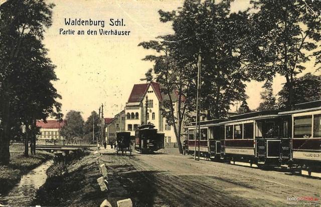 Lata 1898-1903  Plac Grunwaldzki początek XX wieku. Po lewej stronie znajduje się dziś chodnik, jeden z najbardziej uczęszczanych przez wałbrzyszan. Rzeka Pełcznica płynąca przez Plac Grunwaldzki została zakryta po roku 1905 r.   Równolegle do ulicy po lewej stronie został wybudowany po 1910 roku szereg kamienic wraz ze szkołą Królowej Luizy (zbudowana w 1913 roku), która po wojnie została szkołą górniczą.   Na wprost były biurowiec pszczyńskich kopalni wałbrzyskich, wraz z herbem Hochbergów oraz z charakterystycznym młotkiem i żelazkiem, później budynek ZDiK-u.