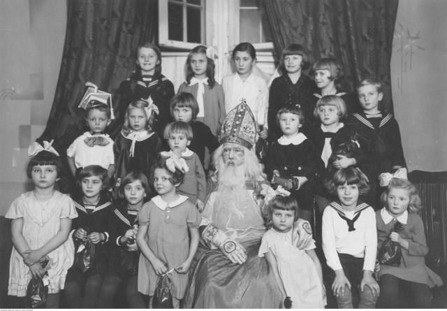 Mikołajki to zwyczaj mający bardzo długą tradycję. Już w średniowieczu dzieci dostawały prezenty od osób przebranych za świętego Mikołaja. Co więcej, jeszcze w XIX wieku był to na ziemiach polskich dzień wolny od pracy! Niektóre z atrybutów świętego Mikołaja również mają długą historię - długa, siwa broda i czerwona szata znane były już w XV wieku. Wtedy oczywiście święty Mikołaj miał jeszcze atrybuty biskupie - szatę oraz mitrę i pastorał. W baśniową postać zaczął powoli przekształcać się na przełomie XIX i XX wieku. A jak wyglądały polskie mikołajki przed laty? Zobacz w naszej galerii!  Gwiazdka dla dzieci w Katowicach, 1934 rok