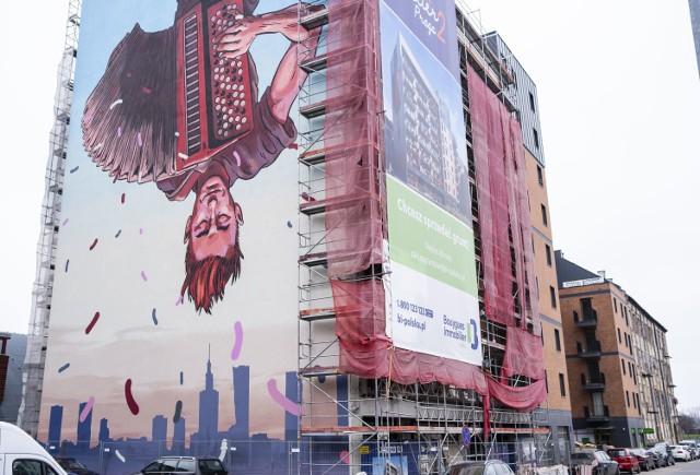 Nowy mural w Warszawie. Uliczny grajek do góry nogami