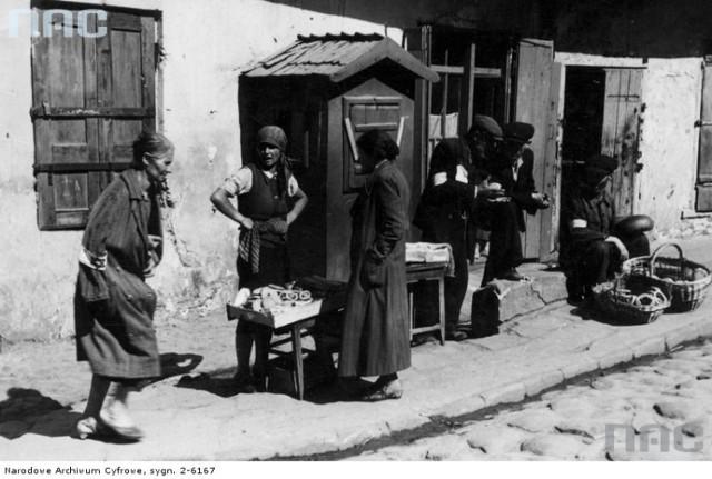 Handel uliczny w getcie. Widoczni handlarze sprzedający pieczywo i słodycze. Data wydarzenia: 1939 - 1945