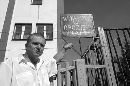 Marek Olkusz pod kontrowersyjną tablicą przy  drutach kolczastych na murze. olgierd gÓrny