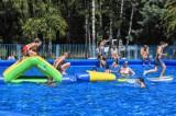 Szamotuły. Mieszkańcy i mieszkanki wypoczywają na Piaszczychach. Na basenie letnim działa wodny tor przeszkód