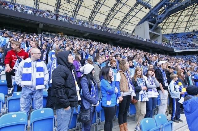 Kibice na stadionie Lecha Poznań oglądają mecz z Widzewem na telebimach.