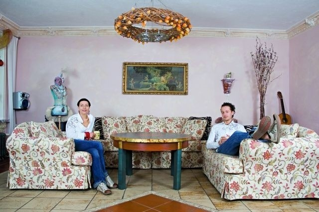 W dużym liliowym salonie honorowe miejsce zajmują kwieciste kanapy.