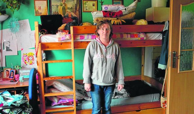 Pani Bożena w  niewielkim  pokoju, który jest jednocześnie sypialnią dla niej, jej męża i dwóch córek. W takich warunkach muszą jadać posiłki, a córki uczyć się i ćwiczyć, by walczyć z chorobą