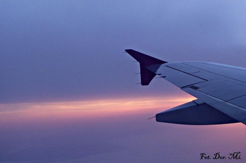 Z maleńkiego okienka samolotu, wschodzące słońce.