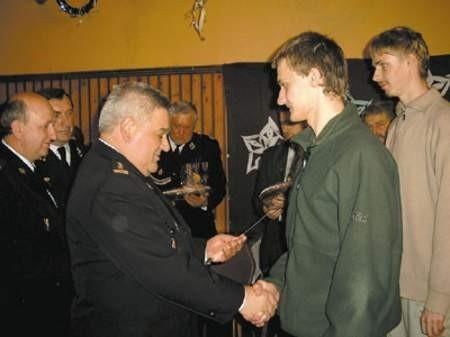 Zastępca komendanta wojewódzkiej komendy PSP, st. brygadier Czesław Kozak, wręcza nagrodę Michałowi Bieńkowi - zwycięzcy Turnieju Wiedzy Pożarniczej.