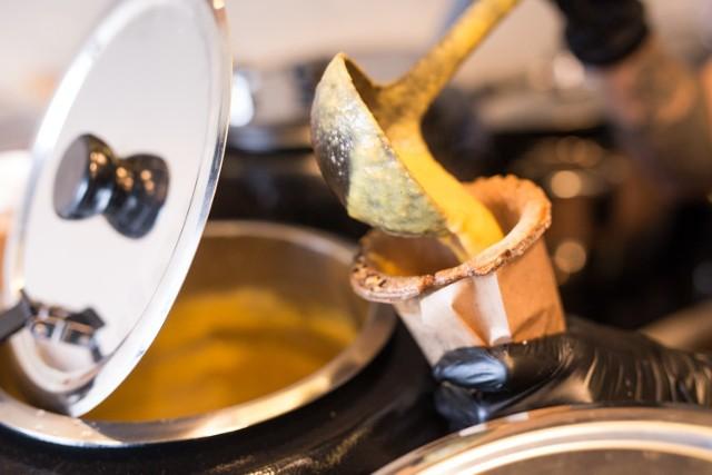 """To unikalne miejsce, w którym zupę zjemy razem z kubkiem.  Możemy wybrać nie tylko smak zupy, ale także rodzaj kubka. Te wykonane są ze specjalnego ciasta z dodatkiem różnorodnych ziaren. Na co dzień w lokalu są cztery rodzaje zup w tym codziennie inna, tzw. """"danie dnia"""". Pomidorowa, soczewicowa, serowa, wegańska czy wegetariańska. Ceny  zaczynają się od 10 zł i kończą na 14 zł. W ofercie są też zestawy lunchowe, na które składa się dodatkowo napój i zdrowe słodkości – kulki mocy."""