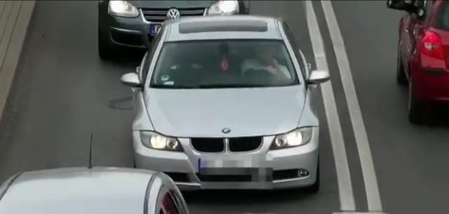 Kadr z filmu nagranego przez policyjny dron - kierowca prowadzi rozmowę w czasie jazdy, wykorzystując telefon trzymany w ręku