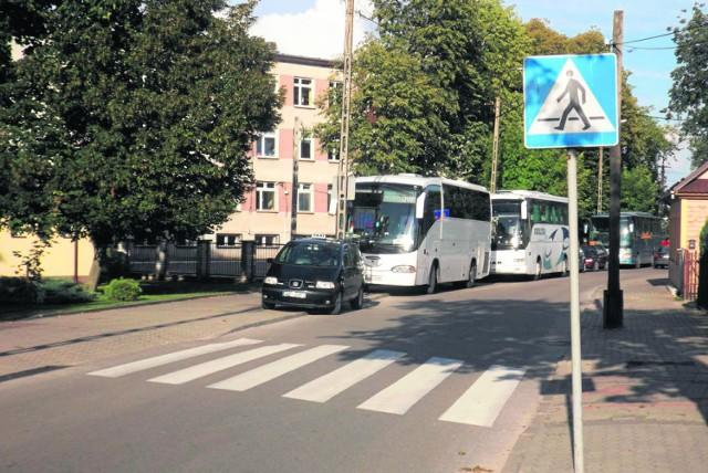 Pojazdy stojące wzdłuż drogi  utrudniają jazdę po wąskiej ulicy Poniatowskiego.
