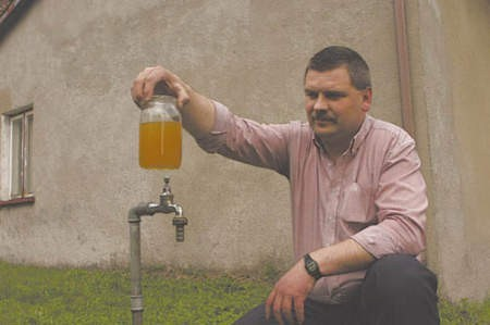Krzysztof Bialik pokazuje zanieczyszczoną wodę, która nie nadaje się ani do picia, ani do kąpieli.