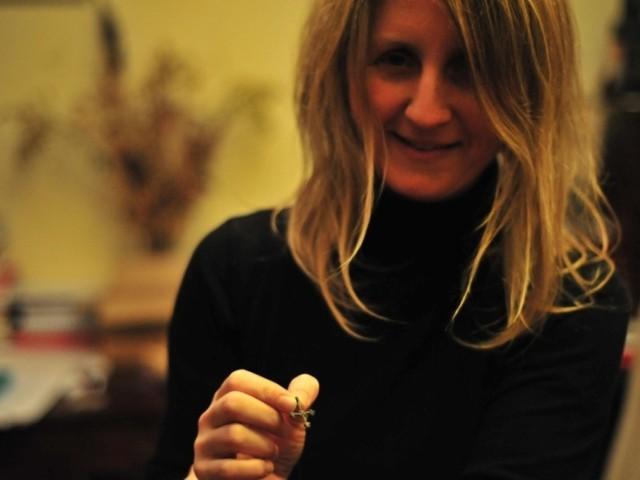 Kryżyk z brązu - zawieszka wczesnosłowiańska w dłoni archeolog Anny Siwiak. Podobny znaleziono w Grucznie