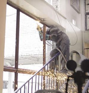 Grzegorz Kapuściński wycina palnikiem stare metalowe ramy okienne.