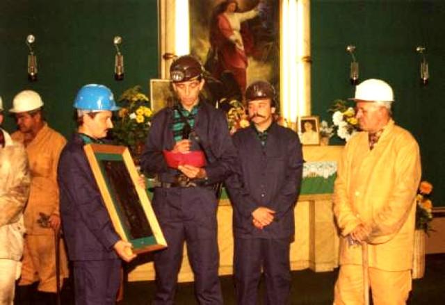 """Na pamiątkę pobytu w kopalni """"Marcel"""", delegacja związków zawodowych przekazuje arcybiskupowi Damianowi Zimoniowi w imieniu załogi  płaskorzeźbę wykonaną z węgla."""
