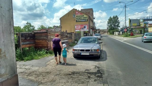 Piesi mają problem - muszą przemieszczać się między ogrodzeniami oraz budynkami a sznurem samochodów stojących na chodniku.
