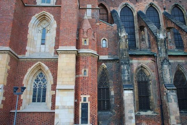 Kamienna głowa znajduje się na południowej wieży katedry wrocławskiej, w centrum kadru, u góry.