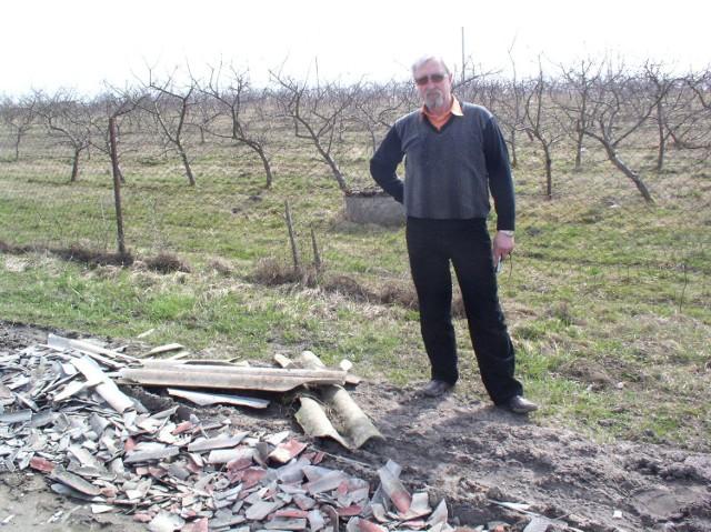 Bogusław Szyca na tle swojego ekologicznego sadu. Przed nim odpady azbestowego eternitu