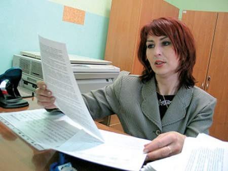Małgorzata Górecka, pracownik socjalny MOPR w Piekarach Śląskich pokazuje druki na świadczenia rodzinne. Lucyna Usińska
