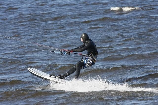 Chłód to akurat żadna przeszkoda dla kitesurferów, którzy wykorzystali mocne podmuchy wiatru, by śmigać na wodach zatoki.