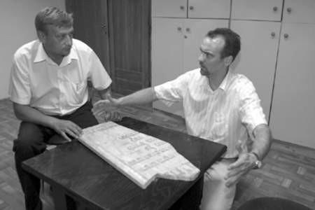 Adama Szydłowski i Mirosław Starzyński pokazują odnalezioną tablicę z bożnicy.
